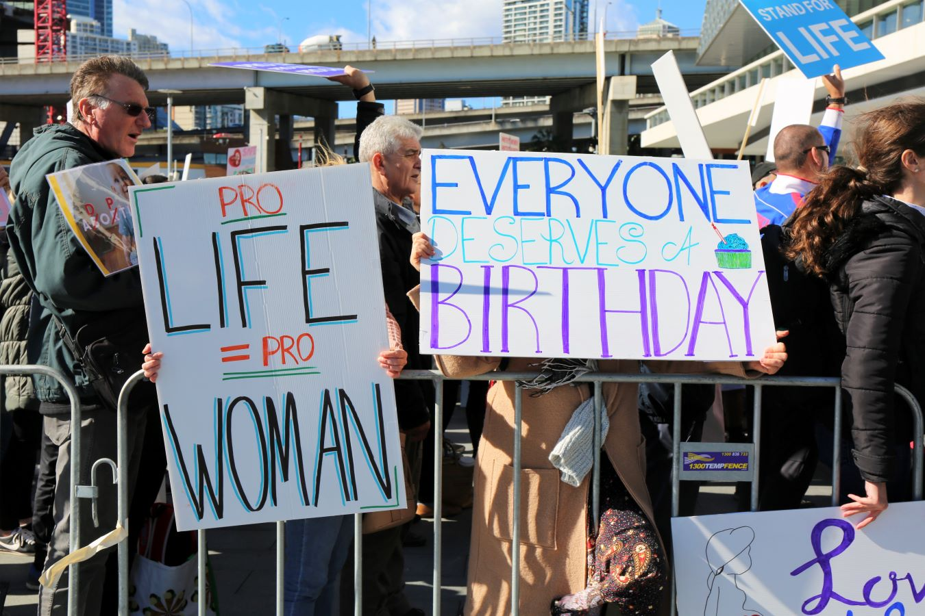 Two women in a crowd holding signs saying 'Pro-Life is Pro-Woman' and 'Everyone Deserves a Birthday'